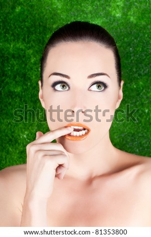 Closeup portrait of a beautiful nervous woman biting her finger while looking up isolated on green - stock photo
