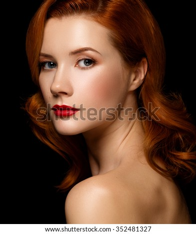 Closeup portrait of a beautiful red-haired girl half-turned over black background. - stock photo