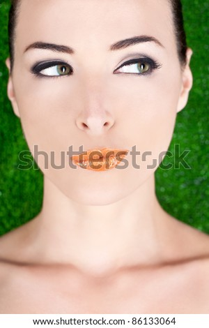 Closeup portrait of a beautiful suspicious woman looking away in studio against green - stock photo