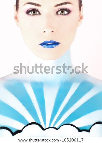 Closeup portrait of a beautiful woman with sky painted on her body isolated on pink background - stock photo