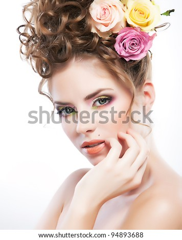 Closeup portrait of a beautiful  young female holding her face in hand over white background. Fresh roses - stock photo