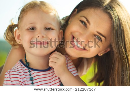 Closeup portrait of a beautiful young mother and her little baby - stock photo