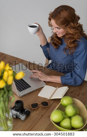Closeup portrait of a beautiful young redhead woman working using laptop and drinking coffee at her desk at office  - stock photo