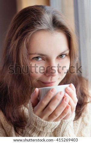 Closeup portrait of a beautiful young woman having coffee. - stock photo