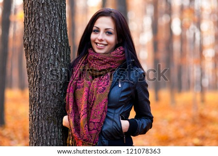 Closeup portrait of a beautiful young woman leaning on a tree trunk in the woods - stock photo