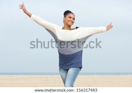Closeup portrait of a beautiful young woman with cheerful expression and arms outstretched walking at the beach - stock photo