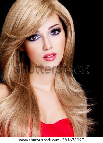 Closeup portrait of a beautiful young woman with long white hairs and red lips. Fashion model posing at studio over black background - stock photo