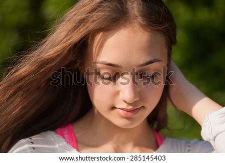 Closeup portrait of a brunette beauty outdoors. - stock photo