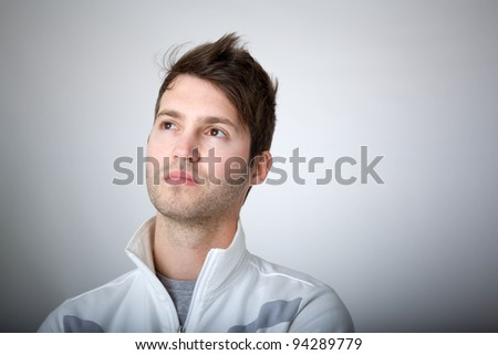 Closeup portrait of a casual young pensive man looking up. - stock photo