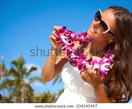 Closeup portrait of a charming tan lady smiling. Hawaii woman with flower lei garland of pink orchids. Welcoming Lei on the hawaiian island Honolulu. - stock photo