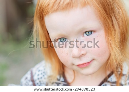closeup portrait of a cute and gentle redhead girl  - stock photo