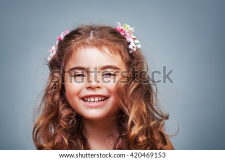 Closeup portrait of a cute cheerful little girl laughing isolated on gray background, precious baby in good mood, happy healthy childhood - stock photo