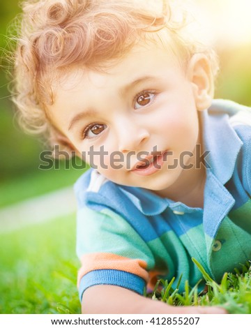 Closeup portrait of a cute little baby boy lying down on the grass, having fun in the park, spending summer holidays outdoors - stock photo