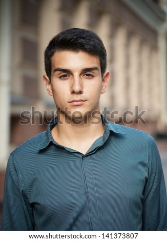 Closeup portrait of a dark-haired youth on the street - stock photo
