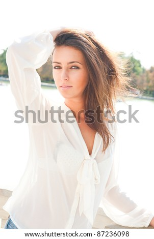 Closeup portrait of a fresh and beautiful young fashion model posing outdoor in sunny weather - stock photo