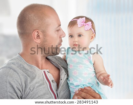 Closeup portrait of a handsome dad with cute little daughter on hands, spending time at home, happy fathers day theme - stock photo