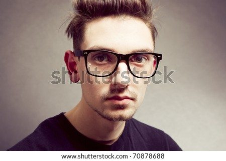 Closeup portrait of a handsome young man wearing glasses - stock photo
