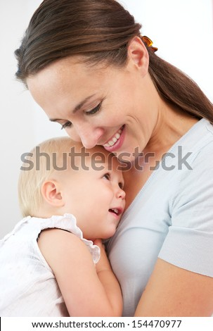 Closeup portrait of a happy mother hugging cute baby against white background - stock photo