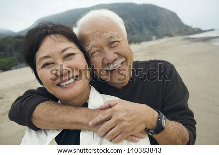 Closeup portrait of a happy senior man embracing woman from behind on the beach - stock photo