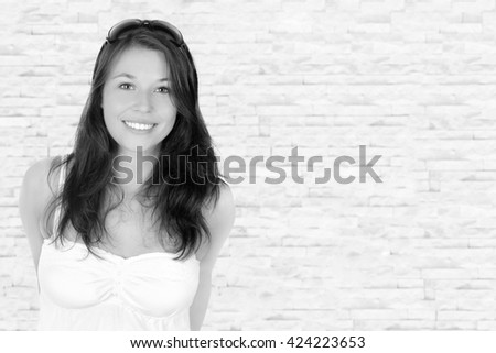 Closeup portrait of a happy teenage girl wearing sunglasses and white top in front of a bright wall, monochrome photo with copy space on the right side of the image - stock photo