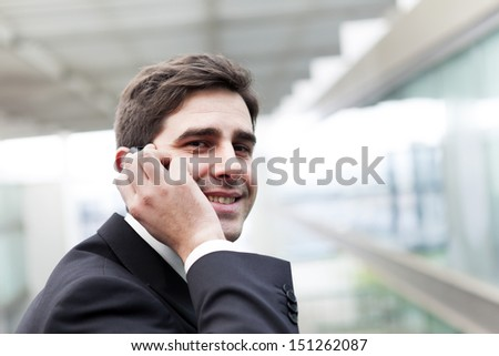 Closeup portrait of a happy young business man talking on cell phone - stock photo