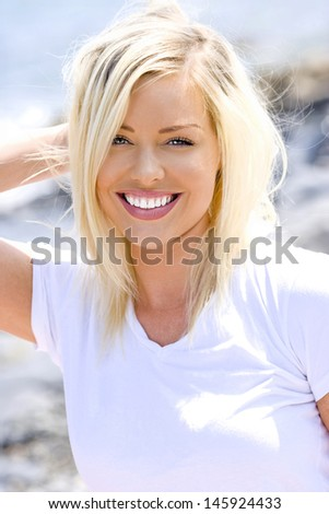 Closeup portrait of a happy young woman with hand up her hair - stock photo