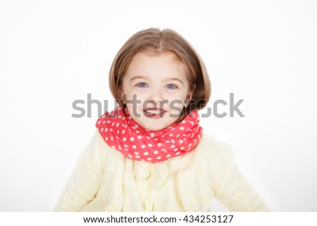 Closeup portrait of a laughing fashion little girl wearing a red scarf and colorful clothes isolated on the white background - stock photo