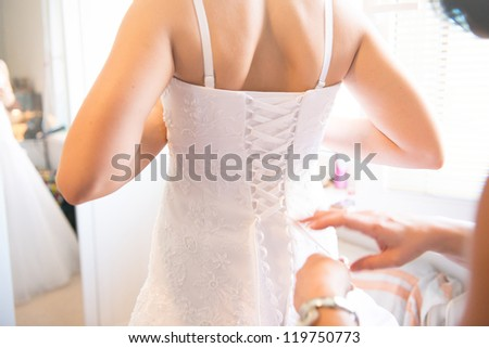 closeup portrait of a maid of honor helping the bride with her dress - stock photo