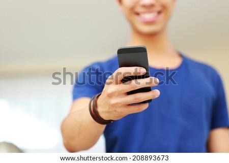 Closeup portrait of a man using smartphone. Focus on smartphone - stock photo