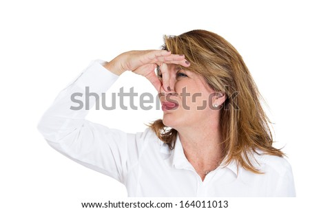 Closeup portrait of a mature beautiful, unhappy woman who covers her nose, looks away, something stinks, very bad smell, situation, isolated on white background. Human facial expressions and emotions  - stock photo