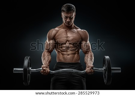 Closeup portrait of a muscular man workout with barbell at gym. Brutal bodybuilder athletic man with six pack, perfect abs, shoulders, biceps, triceps and chest. Deadlift barbells workout.  - stock photo