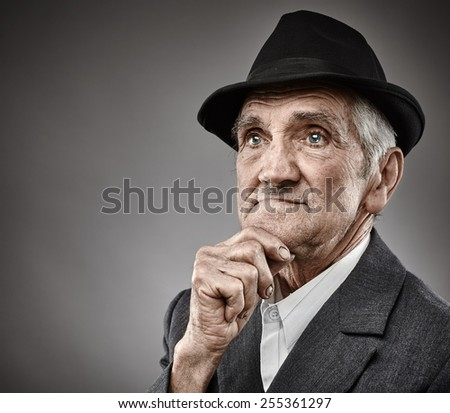 Closeup portrait of a pensive senior man with hand on chin over grey background - stock photo