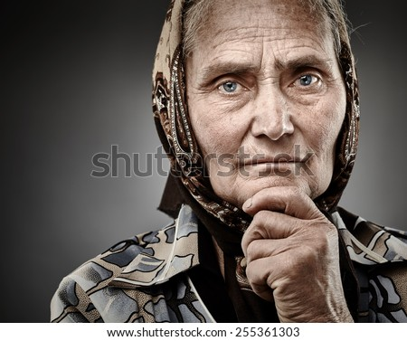 Closeup portrait of a pensive senior woman with hand on chin over grey background - stock photo