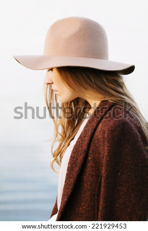Closeup portrait of a pretty blonde girl walking down lakeside. Profile to camera. Wearing hat and jacket. Outside - stock photo