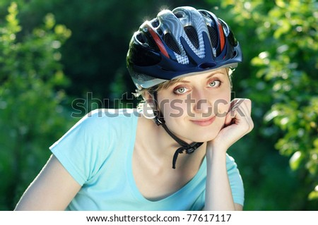 Closeup portrait of a pretty smiling cyclist girl - stock photo