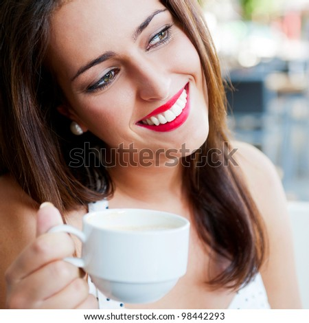Closeup portrait of a pretty young female having a cup of coffee - stock photo
