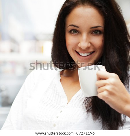Closeup portrait of a pretty young female having a cup of coffee while resting at cafe in shopping mall or airport - stock photo