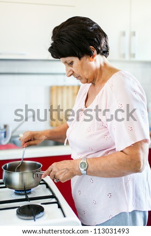 Closeup portrait of a senior woman preparing food on a stove in a kitchen - stock photo