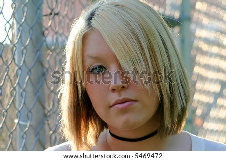 Closeup portrait of a serious teenage girl standing near a chain link fence.  Horizontal format. - stock photo