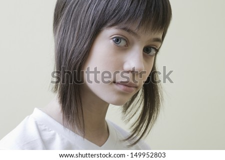 Closeup portrait of a serious young girl with brown hair against colored background - stock photo