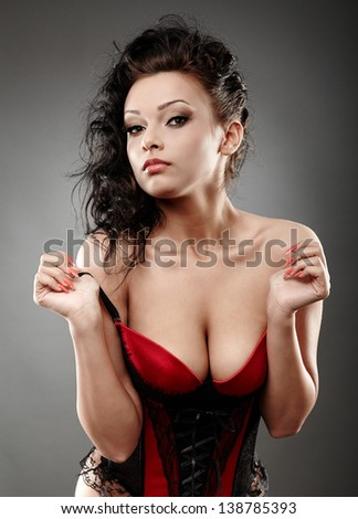 Closeup portrait of a sexy brunette wearing negligee on gray background - stock photo