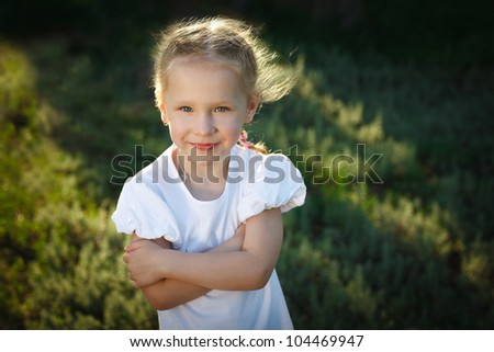 Closeup portrait of a smiling child outdoor over summer grass background - stock photo
