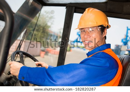 Closeup portrait of a smiling longshoreman looking at camera white driving a working machine  - stock photo