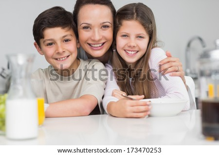 Closeup portrait of a smiling mother with young kids in the kitchen at home - stock photo