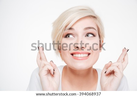 Closeup portrait of a smiling woman with fingers crossed gesture isolated on a white background - stock photo