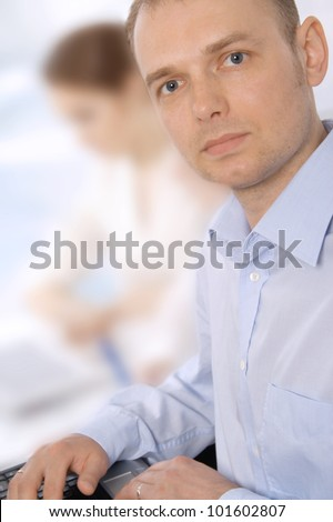 Closeup portrait of a smiling young business man in a meeting with colleagues - stock photo