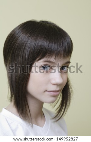 Closeup portrait of a smiling young girl with brown hair against colored background - stock photo