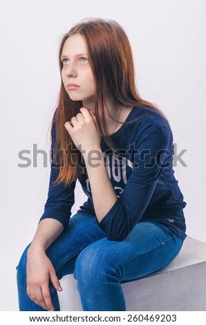 Closeup portrait of a thoughtful young girl on chin against white background - stock photo