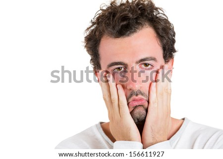Closeup portrait of a very sad, depressed, alone, disappointed, exhausted man resting his face on hands, isolated on white background. Human emotions and facial expressions. - stock photo