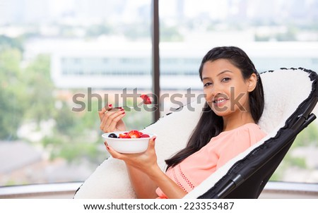 Closeup portrait of a young, attractive businesswoman, eating fruits, berries, nutrition and diet concept, healthy living,  urban lifestyle, Isolated glass window indoor greenery background. - stock photo